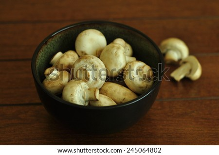 A bowl full of white button mushrooms on wooden background. - stock photo