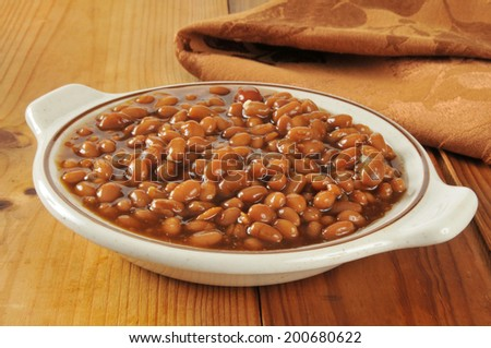 A bowl of barbecue baked beans in a brown sugar sauce - stock photo