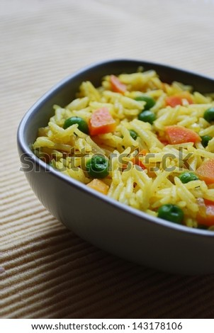 A bowl of basmati rice with yellow curry, carrots and peas - stock photo