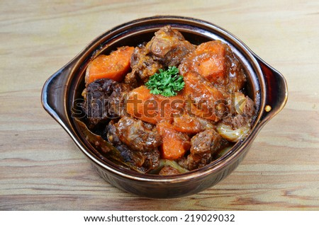 A bowl of beef stew on a wooden table  - stock photo