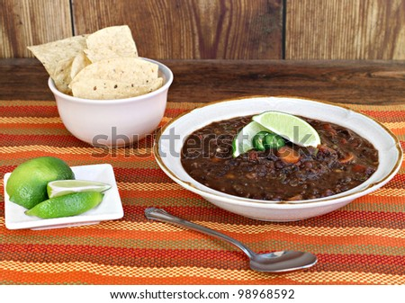 A bowl of black bean soup garnished with jalapeno pepper slices and fresh lime. - stock photo