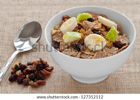 A Bowl of Bran Flakes with Raisins, Sultanas, Banana and Apple  Pieces - stock photo