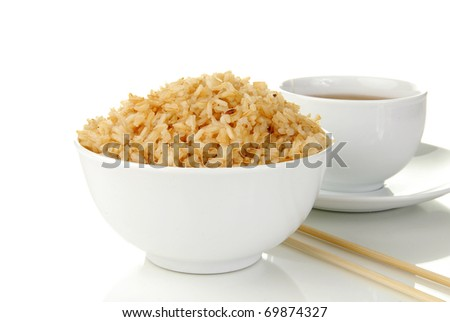 A bowl of brown rice and a cup of tea - stock photo