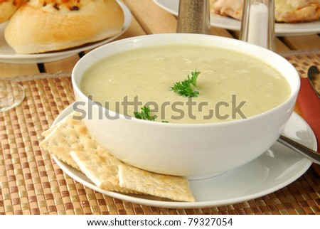 A bowl of celery soup and crackers