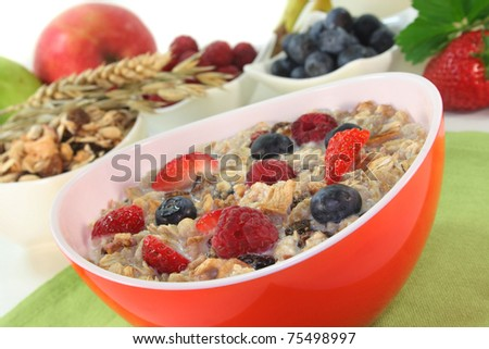 a bowl of cereal with milk, fruit and fresh berries - stock photo