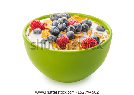A bowl of cereals with blueberries and raspberries with milk on a white background. - stock photo
