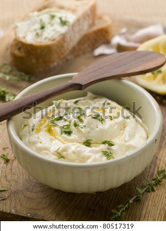 A bowl of cheese dip with thyme and olive oil. Selective focus