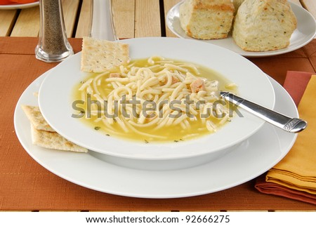 A bowl of chicken noodle soup and soda crackers - stock photo