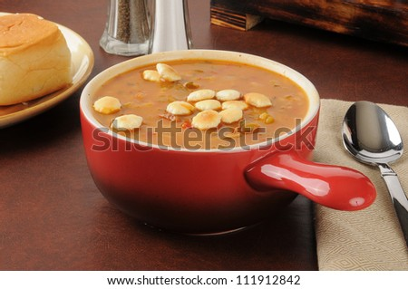 A bowl of chicken rice and sausage gumbo in a red stoneware crock - stock photo