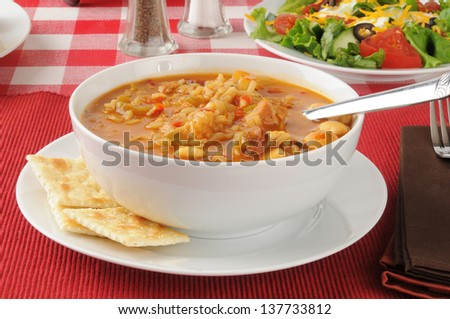 A bowl of chicken sausage gumbo with saltine crackers - stock photo