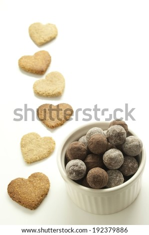 A bowl of chocolates, and some heart shaped crackers. - stock photo