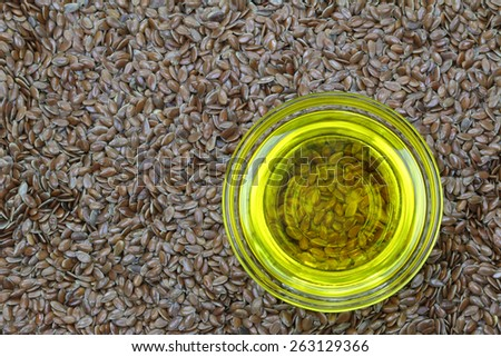 A bowl of cold pressed Linseed yellow oil on flaxseed background. flaxseed are seeds from flax plant  - stock photo