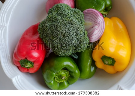 A bowl of colorful red yellow and green peppers with onions and broccoli sits awaiting preparation for a healthy vegetarian delight - stock photo