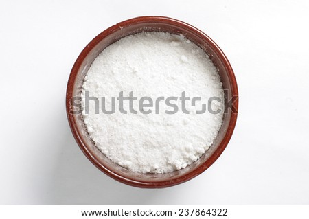 A bowl of common salt isolated on the bright background - stock photo