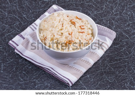 A Bowl of Cooked Rice on a Kitchen Towel  - stock photo