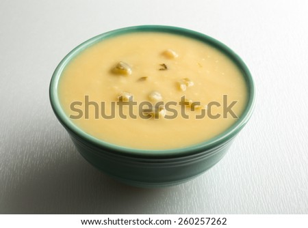 A bowl of cream of celery soup on a white cutting board illuminated by window light. - stock photo
