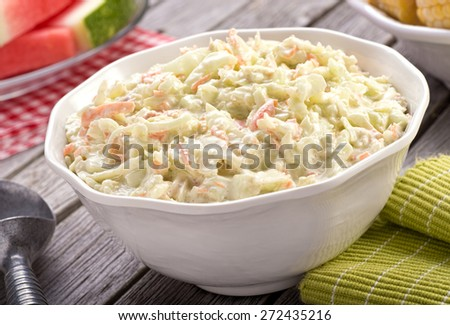 A bowl of delicious creamy homemade coleslaw on a rustic picnic table with watermelon and corn. - stock photo