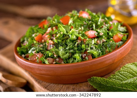 A bowl of delicious fresh tabouli with parsley, mint, tomato, onion, olive oil, lemon juice, and bulgar wheat. - stock photo