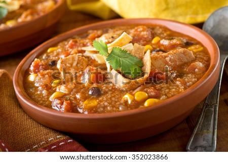 A bowl of delicious home made chicken tortilla soup with chicken, corn, black bean, tomato, homini, and tortilla. - stock photo