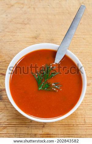 A bowl of delicious tomato soup on a wooden table