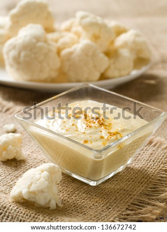 A bowl of dip with fresh cauliflower on background, selective focus