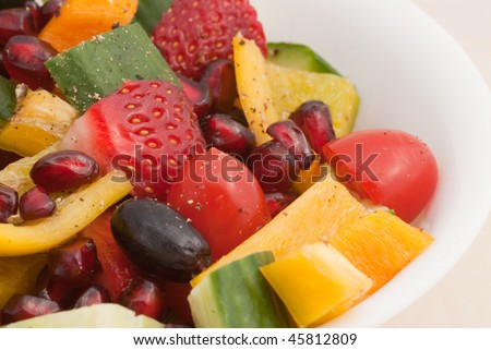 A bowl of fresh fruit and vegetable salad, sprinkled with black pepper dressing
