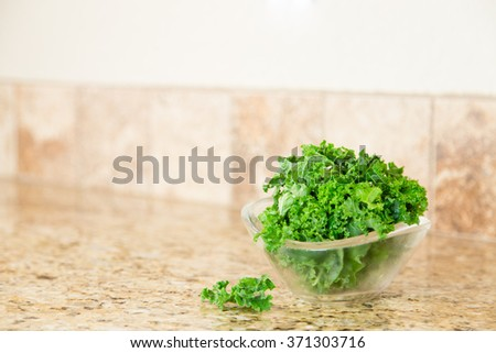 A bowl of fresh green kale in a glass bowl on a granite counter top. Copy space.