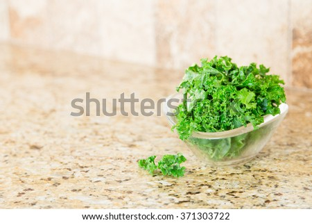 A bowl of fresh green kale in a glass bowl on a granite counter top. Copy space. - stock photo