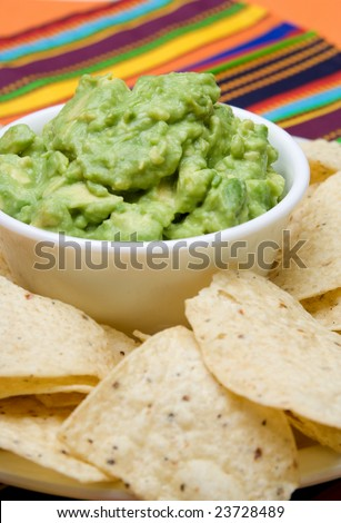 A bowl of fresh guacamole and corn tortilla chips on a colorful background. - stock photo