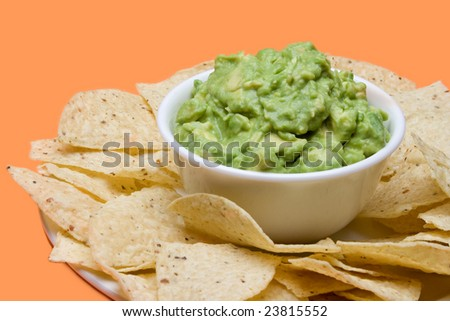 A bowl of fresh guacamole, surrounded by crispy corn tortilla chips. - stock photo