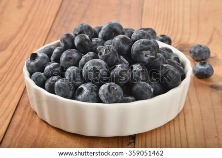A bowl of fresh organic blueberries on a rustic wooden counter - stock photo