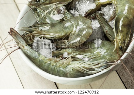 A bowl of fresh raw shrimps cooled with the ice - stock photo