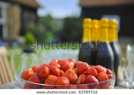 A bowl of fresh strawberries and bottles of champagne