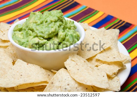 A bowl of freshly made guacamole, surrounded by fresh corn tortilla chips. Colorful background. - stock photo