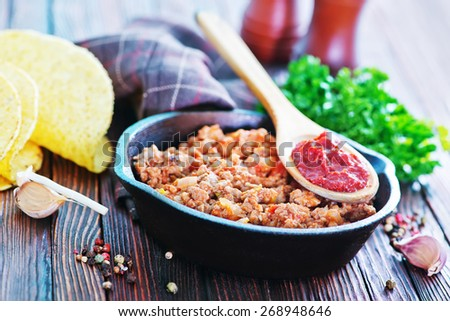 a bowl of fried ground meat with tomatoes ready for tacos - stock photo