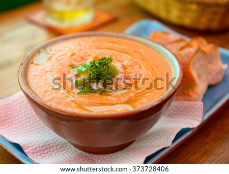 A bowl of gazpacho with bread on a blue plate - stock photo