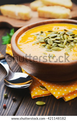 A bowl of homemade creamy pumpkin soup on a wooden table - stock photo