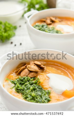 A bowl of homemade creamy pumpkin soup on a wooden table