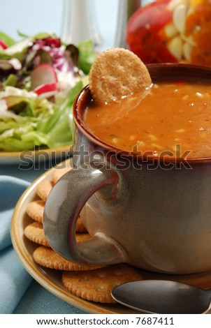 A bowl of hot chicken gumbo with whole wheat crackers and salad - stock photo