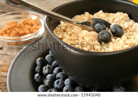A bowl of hot oatmeal with fresh blueberries. - stock photo
