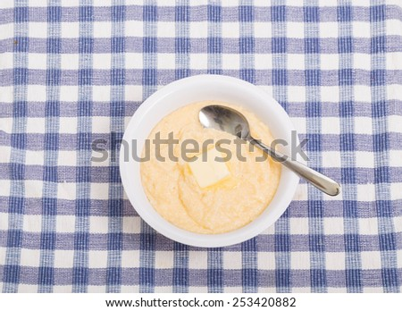 A bowl of hot, yellow grits with a pat of butter melting - stock photo