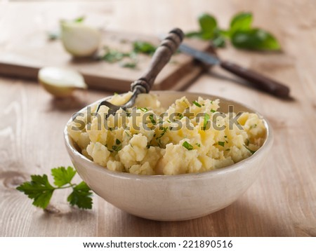 A bowl of mashed potatoes with spoon, selective focus - stock photo