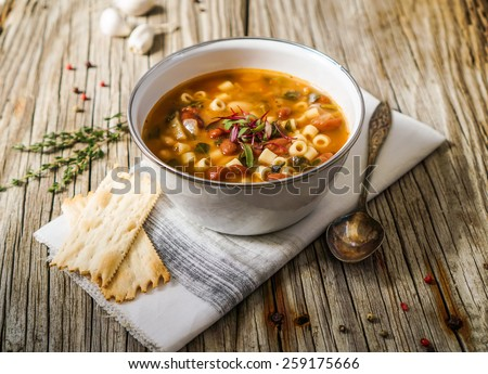A bowl of minestrone soup with crackers on rustic/ vintage background - stock photo