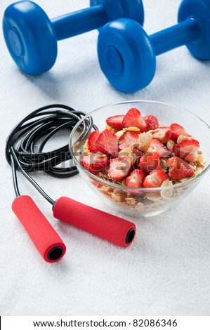 A bowl of muesli with strawberries, a jumping rope and dumbbells, fitness concept - stock photo