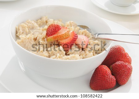 A bowl of oatmeal and strawberries with milk - stock photo