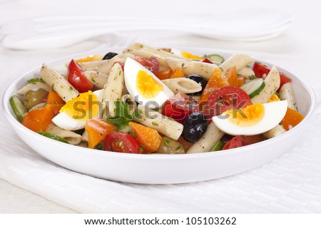 A bowl of pasta salad with egg, tomatoes, cucumber, orange pepper and olives, in a herb dressing.