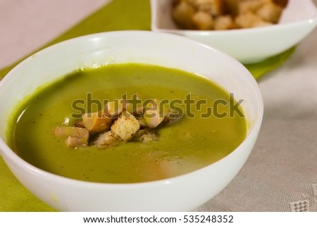 A bowl of pea puree soup served on gray-reddish table cloth with bread croutons and browned sausage