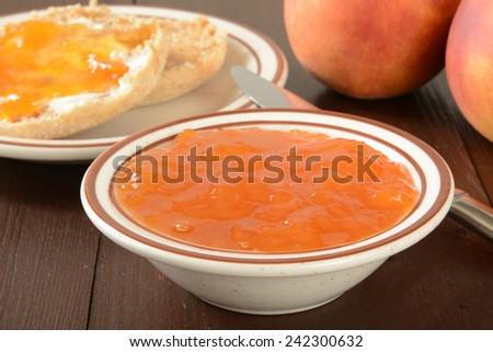 a bowl of peach jam with English muffins in the background, shallow depth of field, focus on jam - stock photo