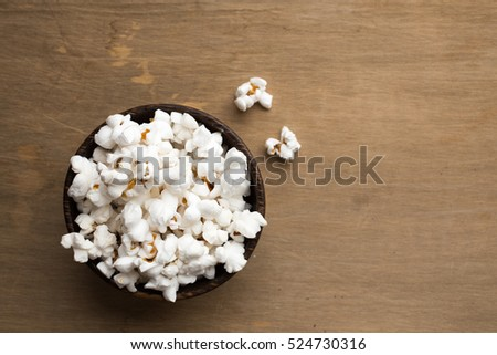 A bowl of pop corn from above with a wooden background.