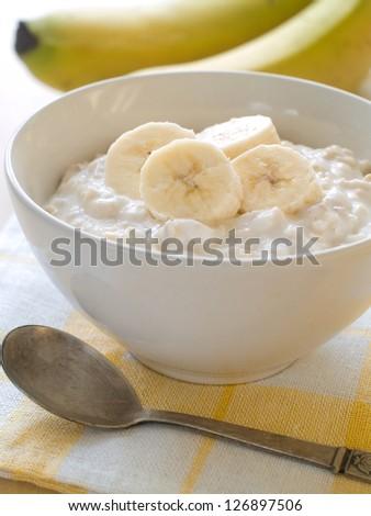 A bowl of porridge with bananas, selective focus - stock photo